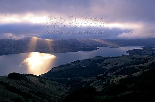 Rays of sun streaming onto Akaroa Harbour, Banks Peninsula, Christchurch City District, Canterbury Region, New Zealand (NZ) stock photo.