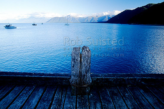Jackson Bay, off the Jackson Bay Wharf. Bpats and yachts in the bay. Haast Range beyond., South Westland, Westland District, West Coast Region, New Zealand (NZ) stock photo.