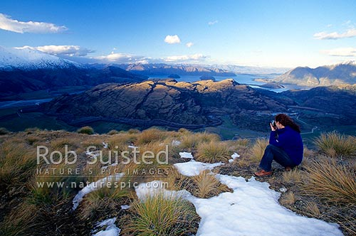 A person looking over Lake Wanaka and Matukituki Valley (left) from the west, in evening. Snow and tussocks, Wanaka, Queenstown Lakes District, Otago Region, New Zealand (NZ) stock photo.