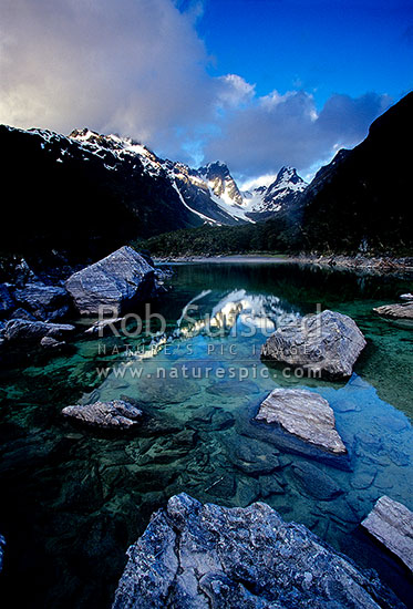 Evening colours on Emily Pass and Emily Peak reflected in Lake MacKenzie, Routeburn Track Great Walk, Fiordland National Park, Southland District, Southland Region, New Zealand (NZ) stock photo.