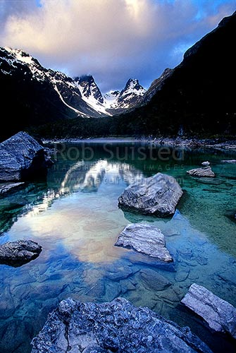 Emily Pass and Emily Peak reflected in Lake MacKenzie, Routeburn Track Great Walk. Evening colours, Fiordland National Park, Southland District, Southland Region, New Zealand (NZ) stock photo.
