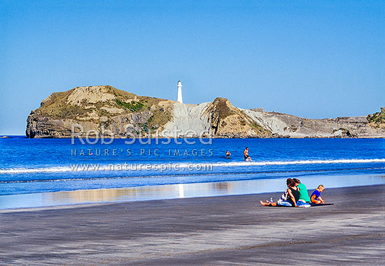 People swimming and playing on Castlepoint Beach. Castlepoint lighthouse behind, Castlepoint, Masterton District, Wellington Region, New Zealand (NZ) stock photo.