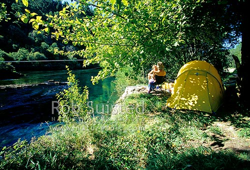 People summer tent camping on the banks of the Waikato River near Taupo, Taupo, Taupo District, Waikato Region, New Zealand (NZ) stock photo.