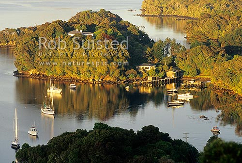 Looking down boats and houses in calm Thule Bay, Paterson Inlet (Whaka A Te Wera) at dawn, Halfmoon Bay, Stewart Island District, Southland Region, New Zealand (NZ) stock photo.
