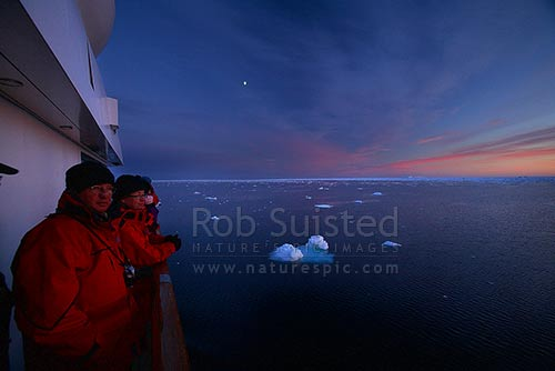 Passengers watching pack ice under the dawn sunrise. 66 degrees South. Expedition ship MV Orion. 66º 2' S 141º34' E, Southern Ocean, Antarctica District, Antarctica Region, Antarctica stock photo.