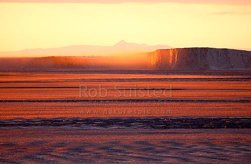 Ice fog rolling off Drygalski Ice Tongue at sunset. Pancake ice covered sea. Prince Albert Mountains behind. Victoria Land, Ross Sea, Antarctica District, Antarctica Region, Antarctica stock photo.