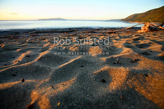 Sunset on Pukerua Bay beach, Kapiti Island behind. Sand patterns and textures, Pukerua Bay, Porirua City District, Wellington Region, New Zealand (NZ) stock photo.