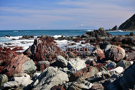 Red Rocks Scientific Reserve (including pillow lavas, volcanic sediments, red cherts). Cook Strait and Kaikoura Ranges beyond, Wellington, Wellington City District, Wellington Region, New Zealand (NZ) stock photo.