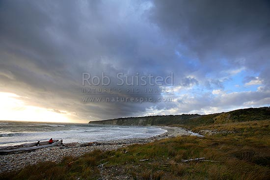 Dramatic evening clouds gathering over the remote southern Waitutu Coast. Sunset, dusk. Wairaurahiri River Mouth. People in distance, Waitutu Forest, Fiordland, Southland District, Southland Region, New Zealand (NZ) stock photo.