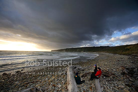 Dramatic evening clouds at dusk gathering over visitors to the remote southern Waitutu Coast, Wairaurahiri. People in foreground, Waitutu Forest, Fiordland, Southland District, Southland Region, New Zealand (NZ) stock photo.