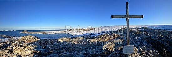 1913 Memorial Cross for Belgrave Ninnis and Xavier Mertz, Azimuth Hill, Mawson's Huts and boat harbour behind, Cape Denison, Commonwealth Bay, George V Land, Antarctica District, Antarctica Region, Antarctica stock photo.