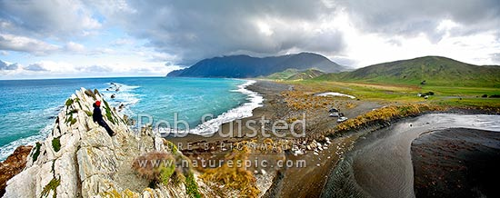 Person above the Whawanui River entering sea at White Rock beach, with moody Aorangi Mountains (Haurangi Forest Park) and Cape Palliser beyond., White Rock, Wairarapa, South Wairarapa District, Wellington Region, New Zealand (NZ) stock photo.