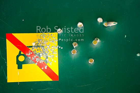 Vandalism damage to a Department of Conservation DOC sign by rifle bullet and shotgun pellets holes, New Zealand (NZ) stock photo.