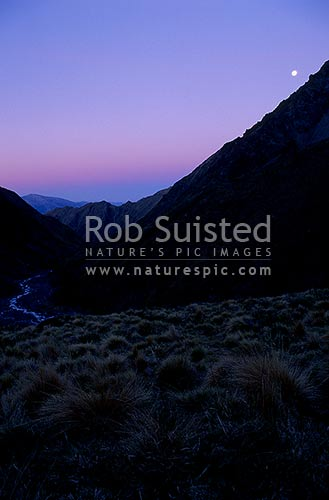 Last rays of evening and moon over the Hodder River, Mount (Mt) Tapuae-o-Uenuku, Inland Kaikoura Ranges, Marlborough District, Marlborough Region, New Zealand (NZ) stock photo.