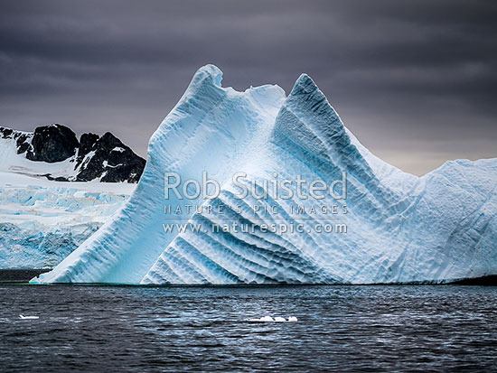 Large iceberg sculptured by water, and ground in the Gerlache Strait, Antarctic Peninsula, Antarctica Region, Antarctica stock photo.