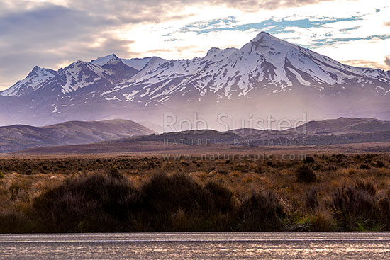Mt Ruapehu (2797m) seen from the Rangipo Desert and SH1 Desert Road. Last rays of sun as storm weather gathers from the south, Waiouru, Ruapehu District, Manawatu-Wanganui Region, New Zealand (NZ) stock photo.
