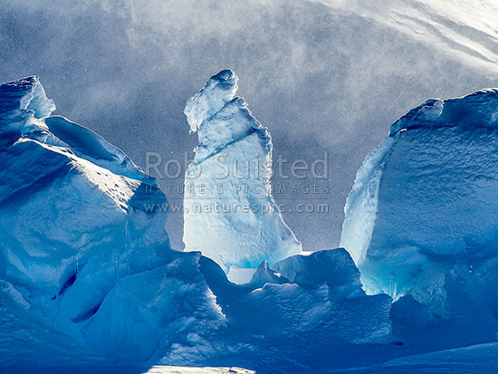 Ice pillar amongst pressure ridges on Ross Ice Shelf coast, Bartlett Inlet. During catabatic blizzard blowing spindrift snow ans ice into air. Blizzard conditions, Ross Sea, Antarctica Region, Antarctica stock photo.