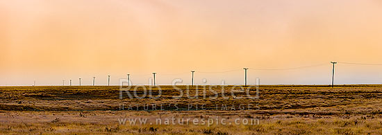 MacKenzie Basin barren high country farmland traversed by powerlines and powerpoles on a moody dawn. Panorama. Abstract, Tekapo, MacKenzie District, Canterbury Region, New Zealand (NZ) stock photo.