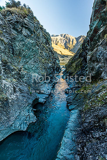 Sixteen Mile Gorge on the upper Shotover River, with Mt Lima (2310m) in the Richardson Mountains beyond. A dramatic cleft in rock carrying the Shotover River. Branches Station, Shotover River Valley, Queenstown Lakes District, Otago Region, New Zealand (NZ) stock photo.